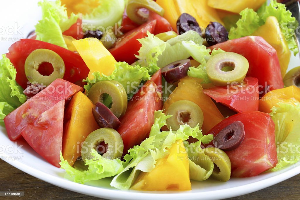 salad of colorful tomatoes and olives on the wooden table royalty-free stock photo
