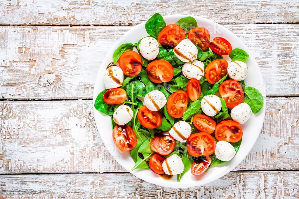 salad of mozzarella, cherry tomatoes and spinach with balsamic sauce stock photo