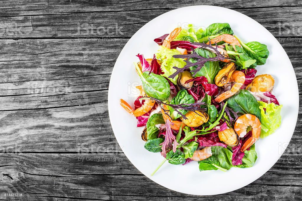 salad of prawns, mussels, lettuce leaves, spinach, arugula, radi stock photo
