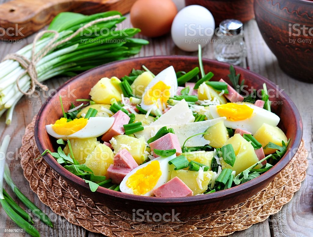 Salad of wild garlic with boiled potatoes, eggs, ham, parmesan stock photo