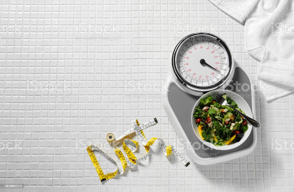 Salad on Bathroom Scales stock photo