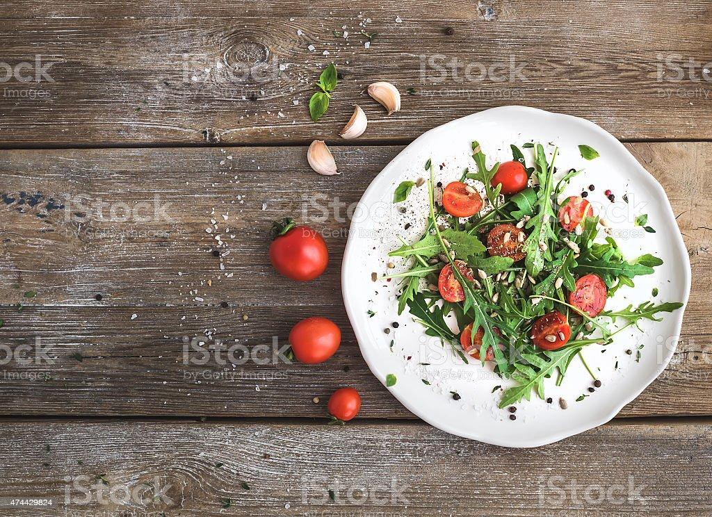 Salad with arugula, cherry tomatoes, sunflower seeds and herbs stock photo