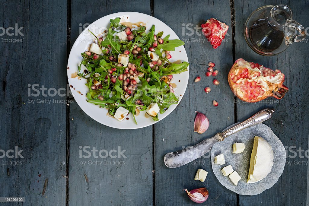 salad with arugula, feta cheese and pomegranate on  rustic wood stock photo