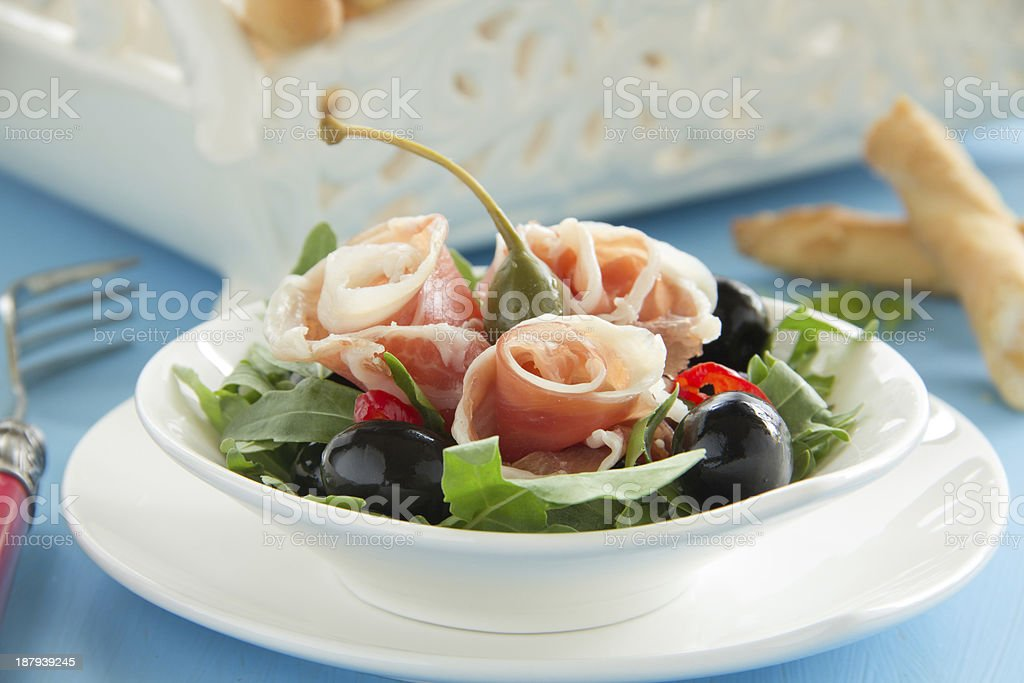 Salad with arugula, prosciutto and olives. royalty-free stock photo