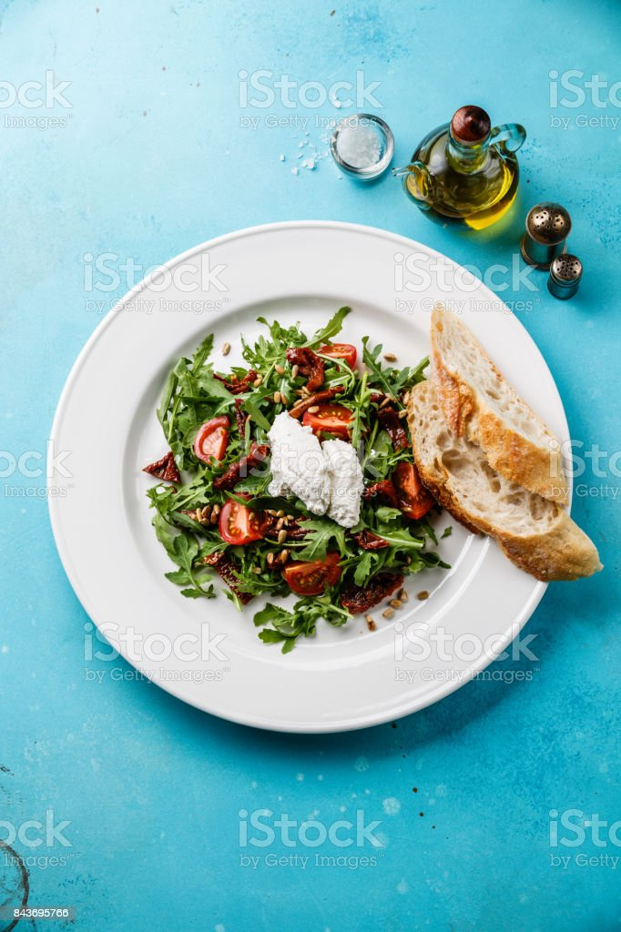 Salad with arugula, sun-dried tomatoes and ricotta cheese stock photo