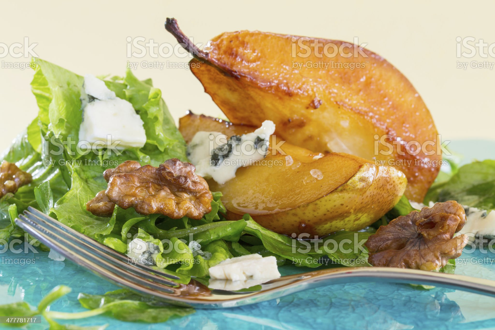 Salad with caramelised pears,walnuts and cheese, on blue plate royalty-free stock photo