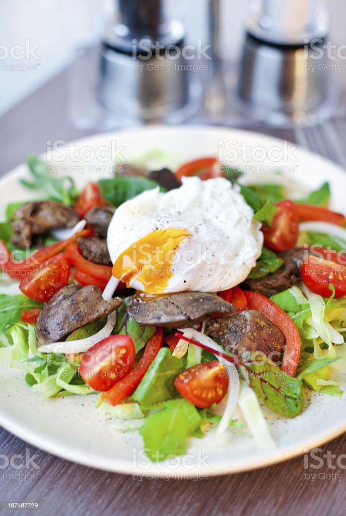 Salad with chicken livers and poached egg royalty-free stock photo