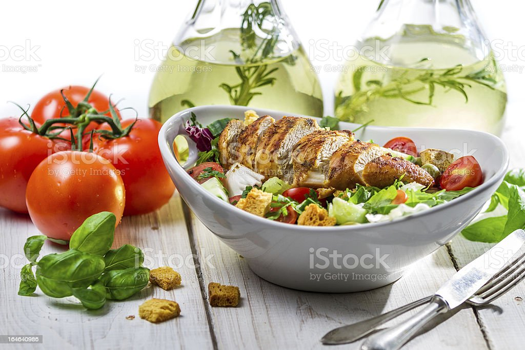 Salad with chicken, tomato, olive and fresh herbs stock photo