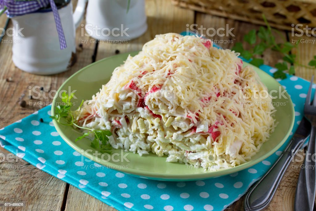 Salad with crab sticks, eggs, cheese and garlic. Festive appetizer on a wooden table. stock photo