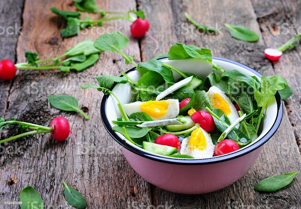 Salad with cucumber, radish, ramson, spinach, boiled eggs stock photo