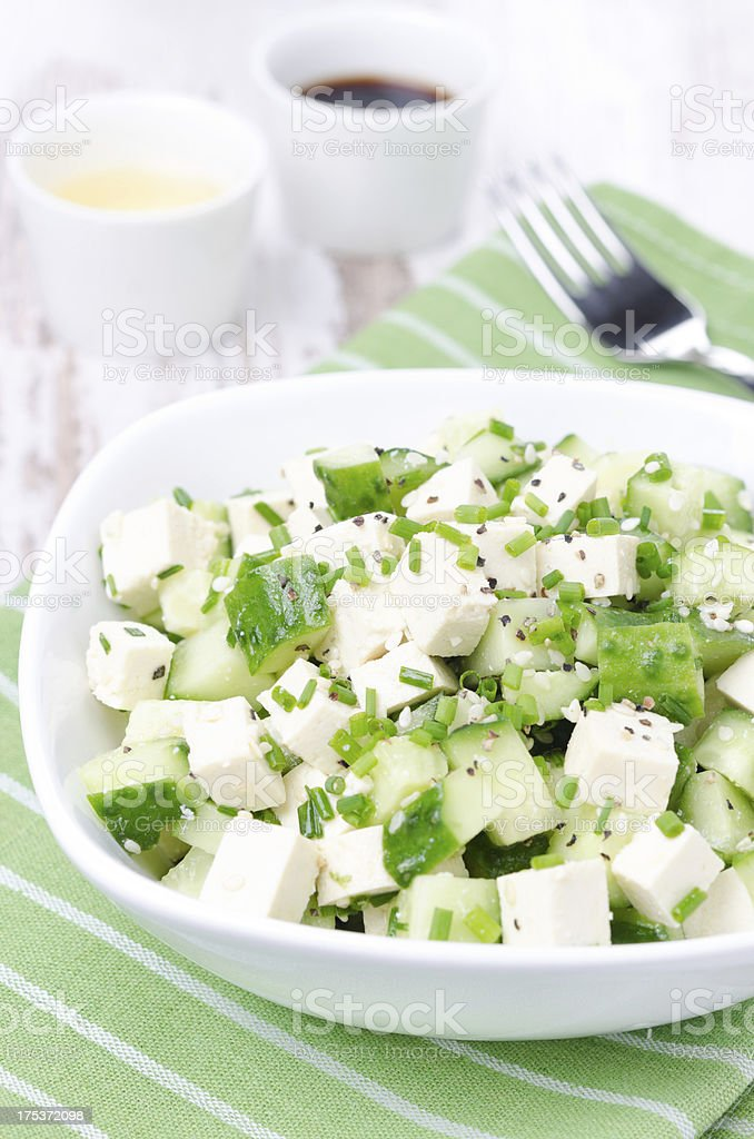 salad with cucumber, tofu, chives and sesame seeds, vertical royalty-free stock photo