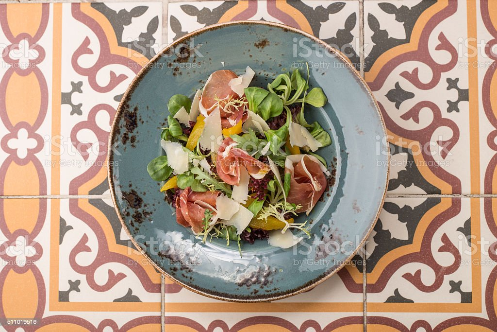Salad with cured ham, fresh vegetables and parmesan cheese stock photo