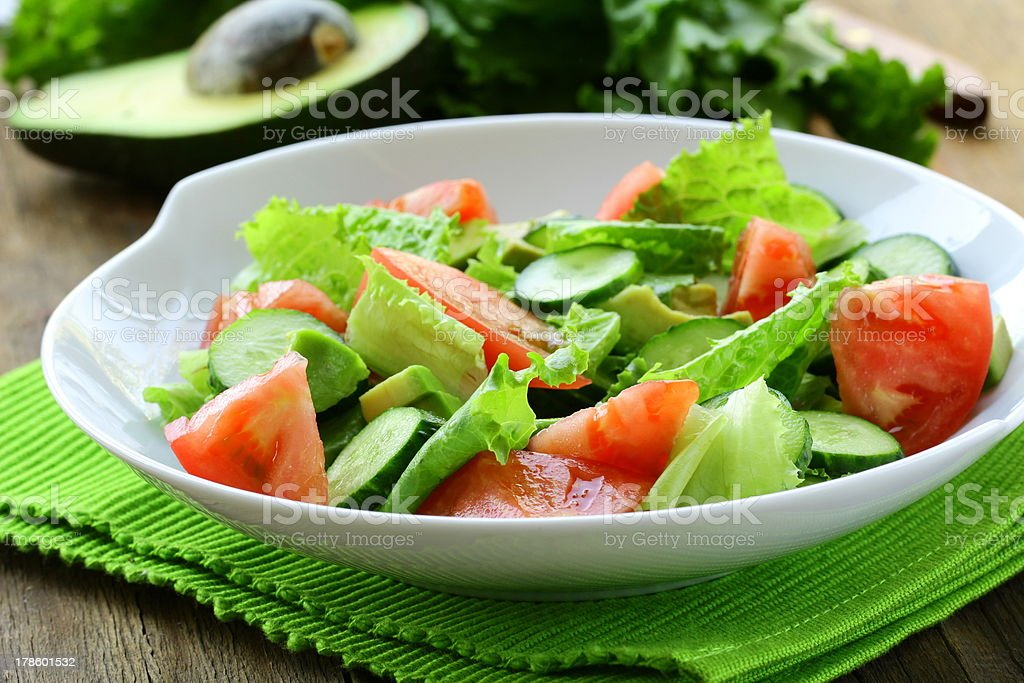 salad with fresh avocado and tomato on a wooden table royalty-free stock photo