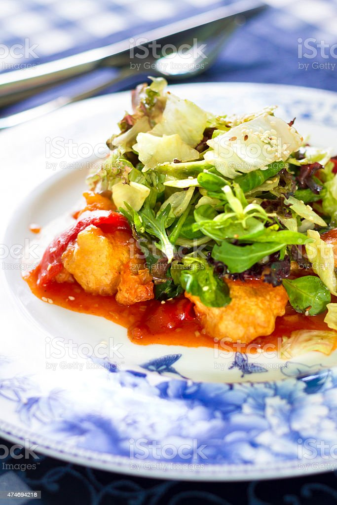 Salad with fried fish fillet, red pepper and salad mix stock photo