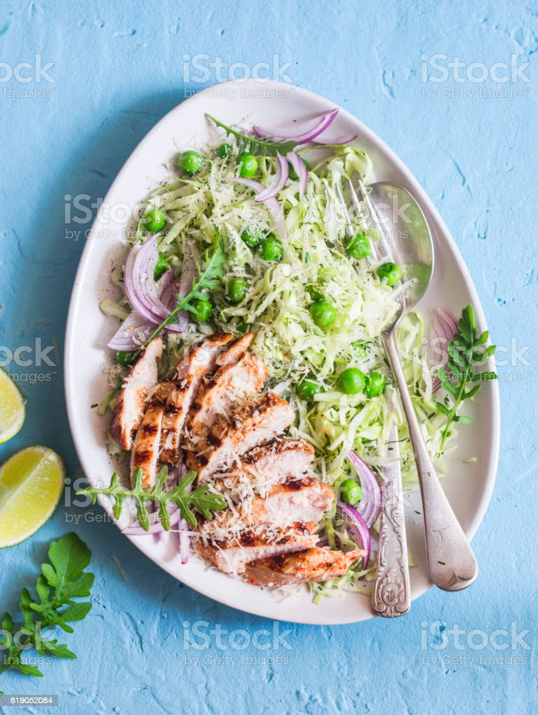 Salad with grilled chicken, cabbage, green peas and parmesan cheese. On a blue background, top view stock photo