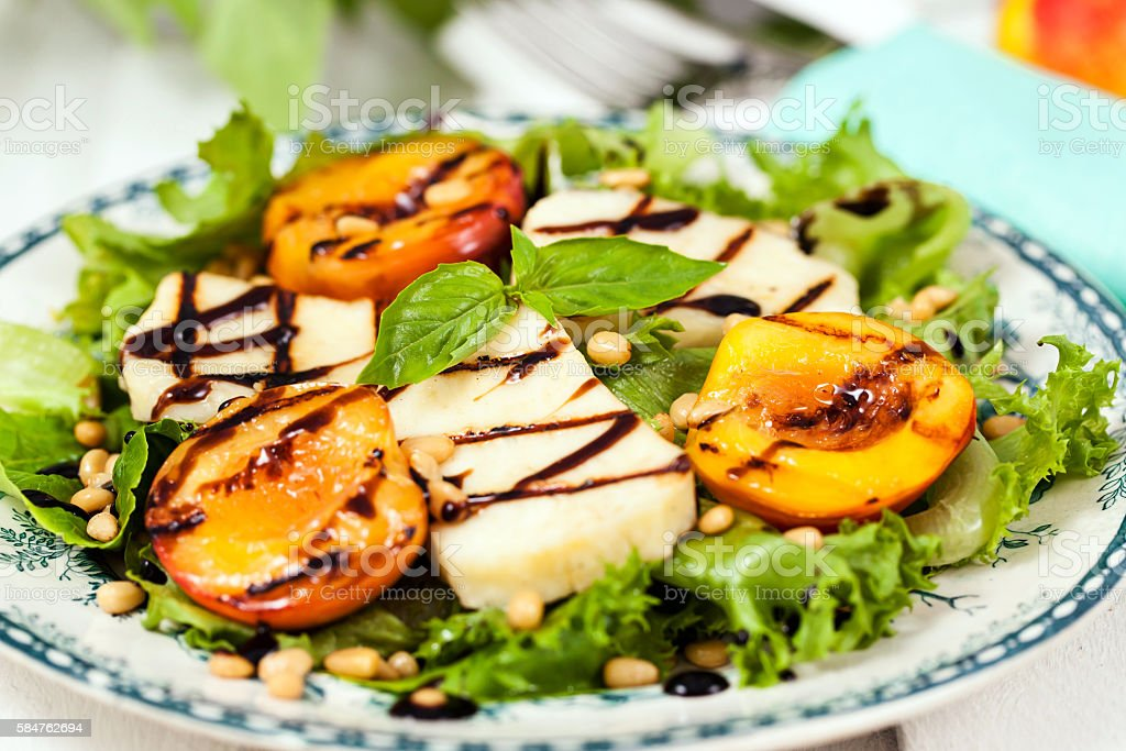 Salad with grilled halloumi cheese and peaches stock photo