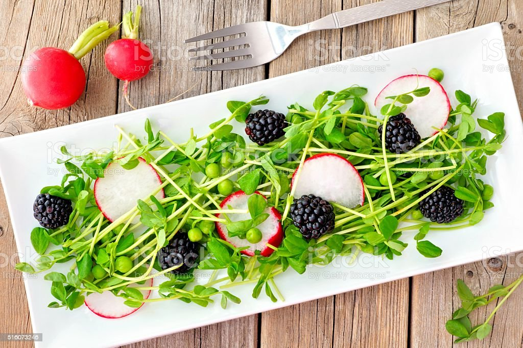 Salad with pea shoots, radishes, blackberries on rustic wood stock photo