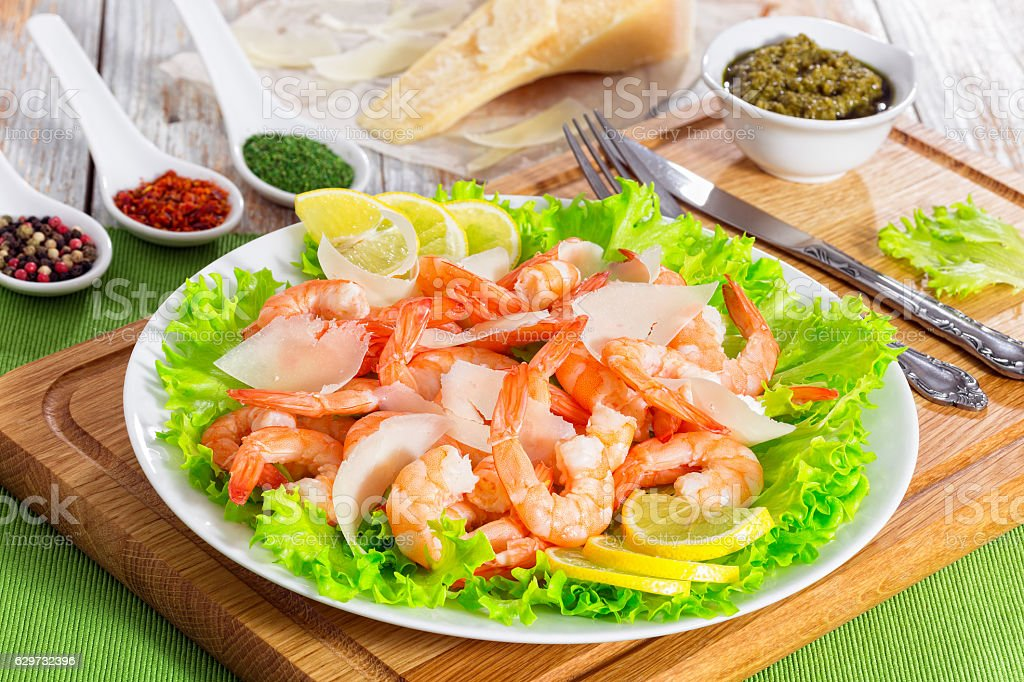 salad with prawns, lettuce, slices of parmesan cheese and lemon stock photo