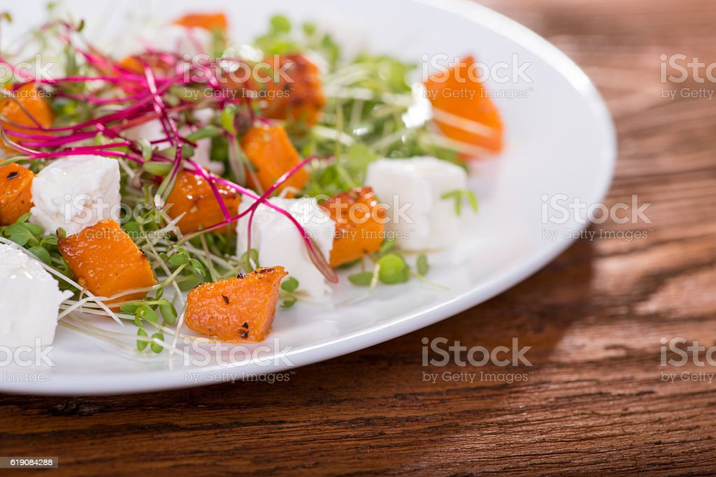 Salad with roasted pumpkin, cheese and herbs mini stock photo