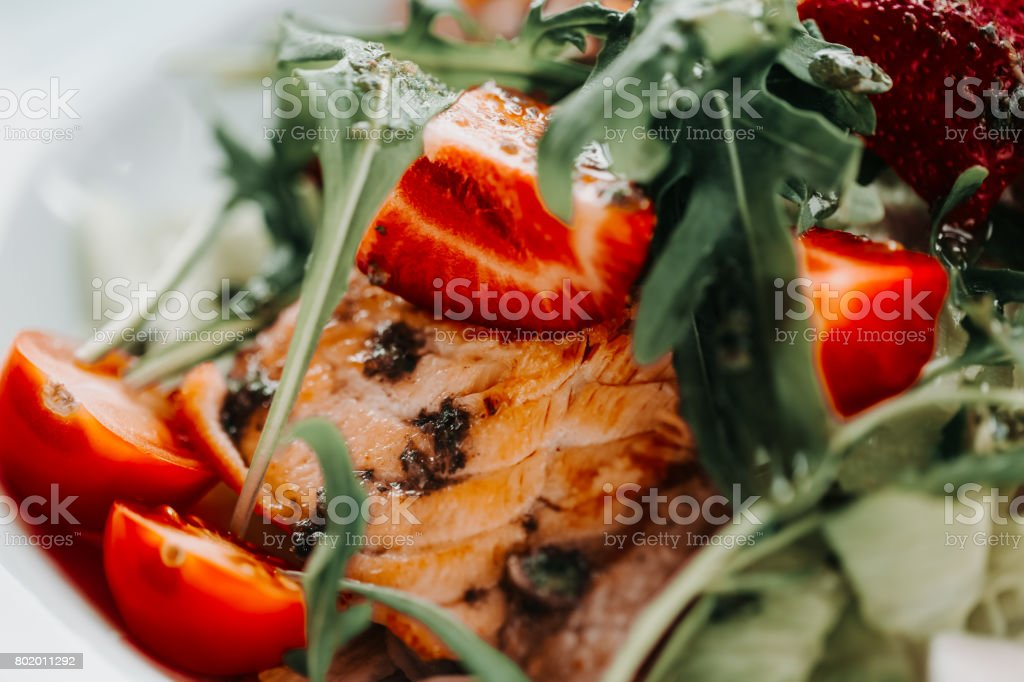 salad with salmon on white plate. Lifestyle healthy eating Food photo concept. macro strawberry in focus stock photo