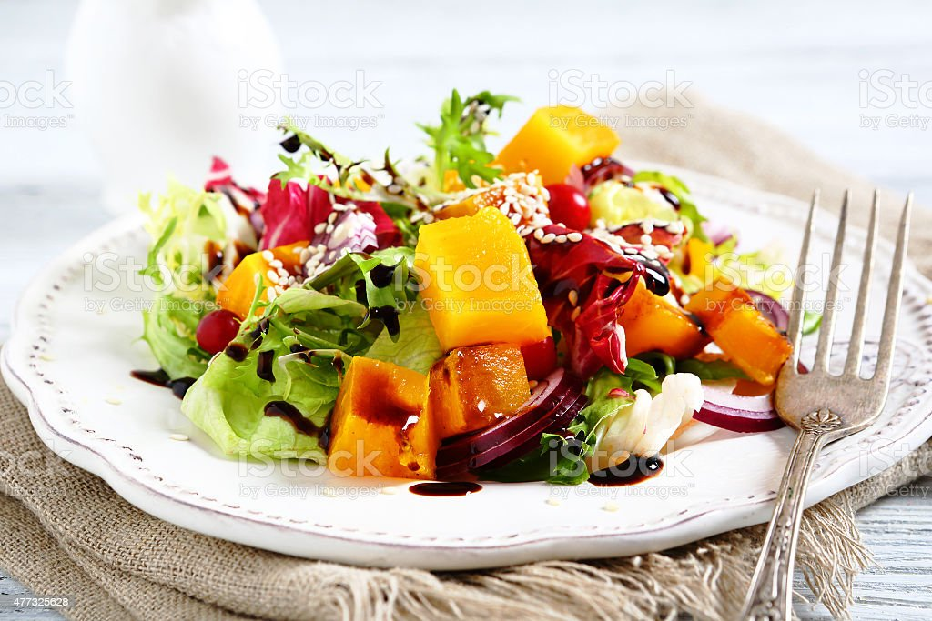 Salad with slices of pumpkin on a plate stock photo