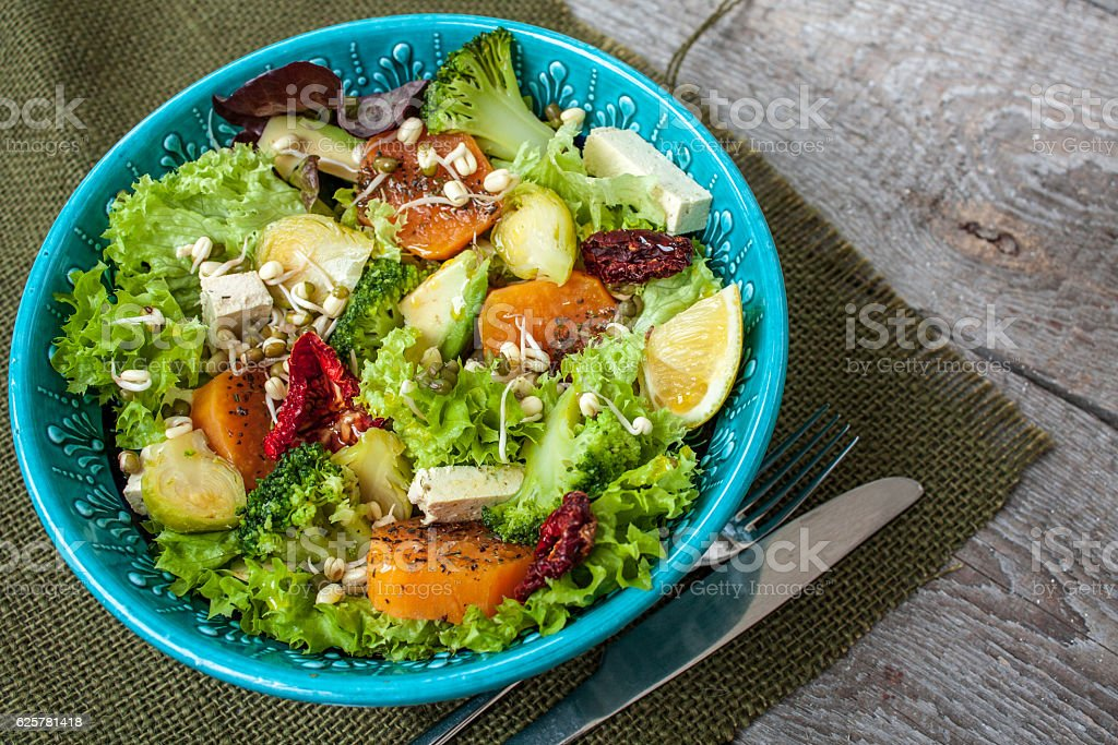 Salad with sweet potatoes, dried tomatoes, avocado, broccoli stock photo