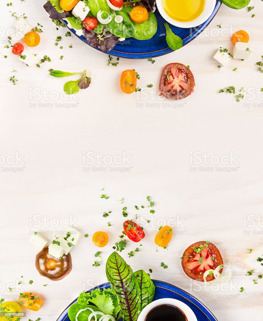 salad with tomatoes, greens, dressing and feta cheese, frame stock photo