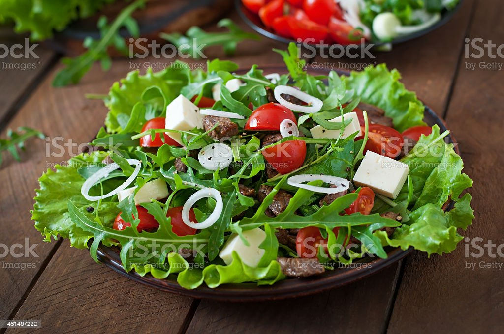Salad with veal slices, arugula, tomatoes and feta cheese stock photo