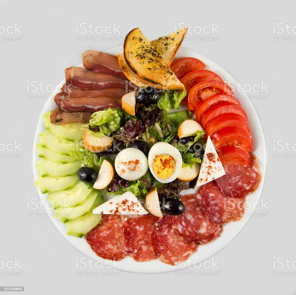 Salad with vegetables, egg, cheese and sausage. stock photo