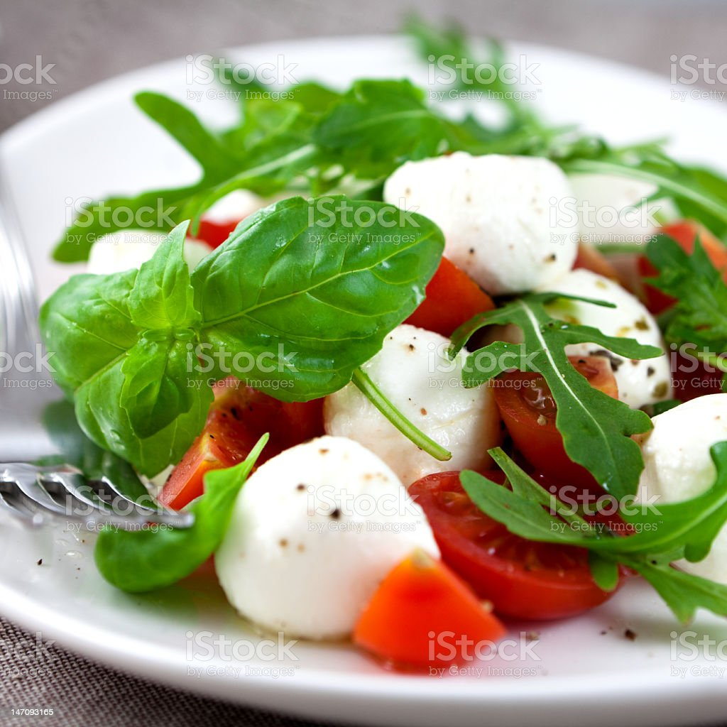 Salad with white mozzarella cheese balls on a white plate royalty-free stock photo