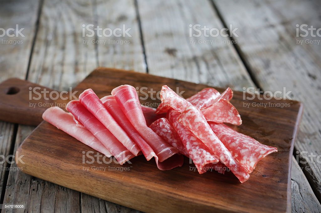 Salami and sliced meat on the wooden board, appetizer, italy stock photo