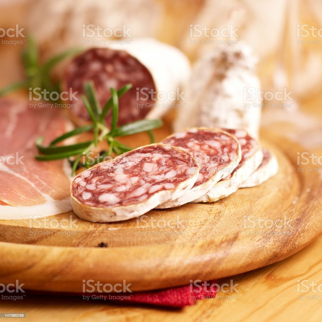 Salami cut on a wood board with rosemary garnish royalty-free stock photo