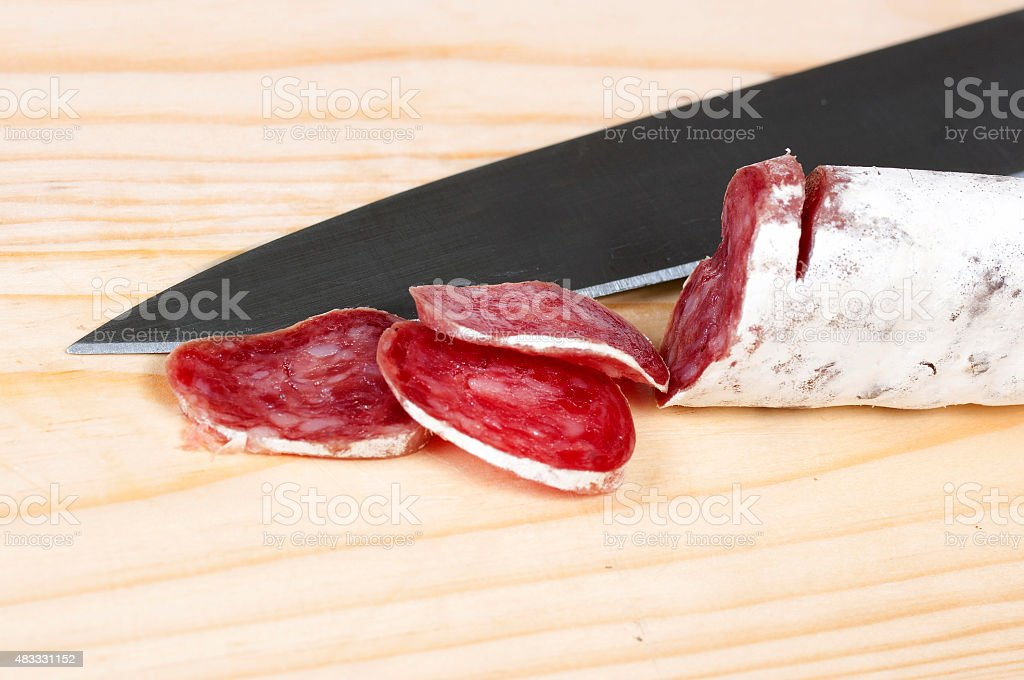 salami cut with  knife on a cutting board stock photo