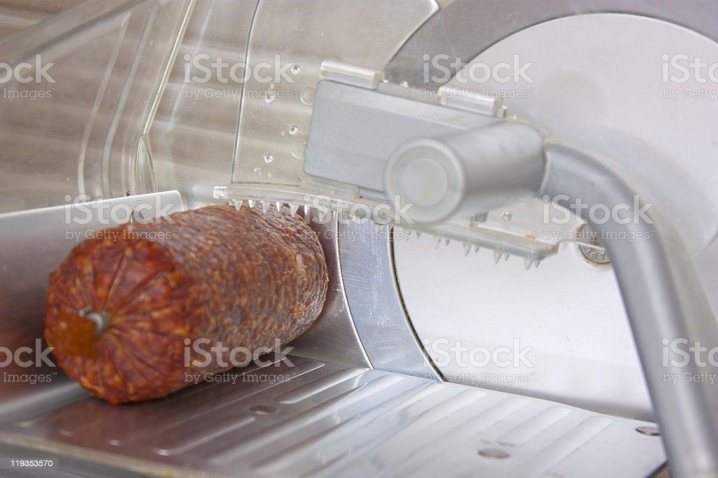 Salami on slicer stock photo