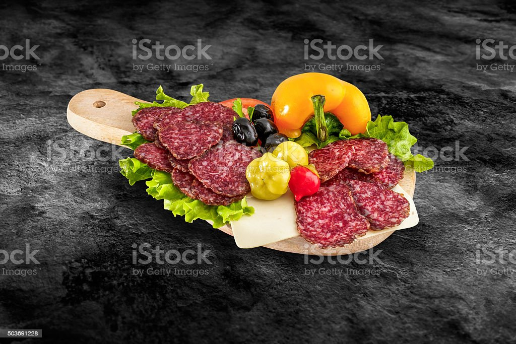 Salami sausage slice and vegetables. Wooden board with clipping path stock photo