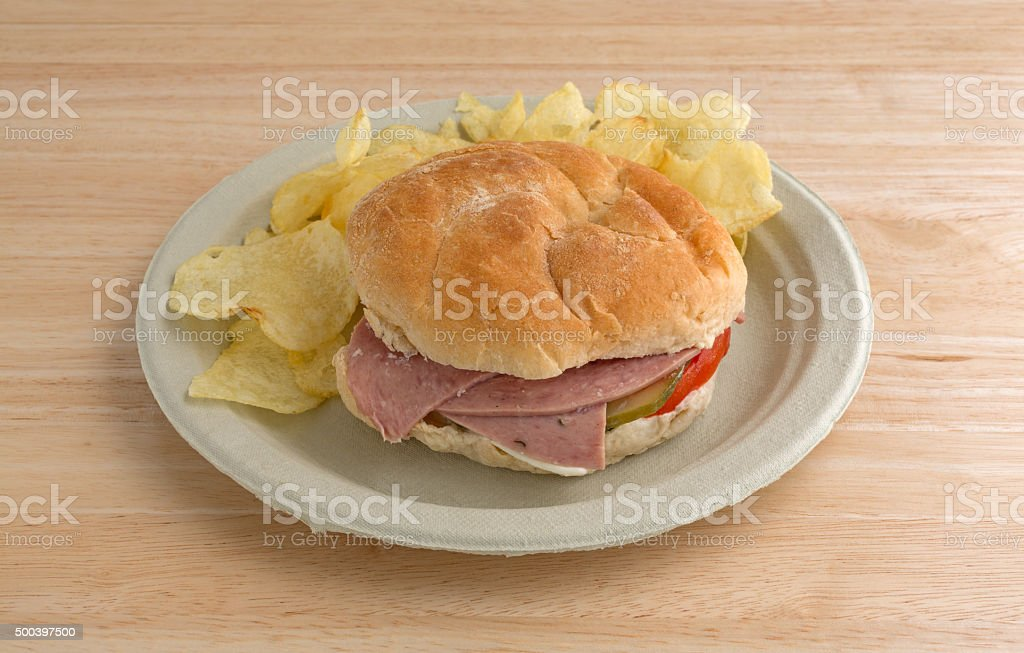 Salami sub sandwich on plate with chips on table stock photo