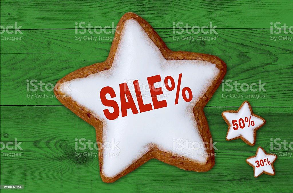 Sale cinnamon star on green wood background stock photo