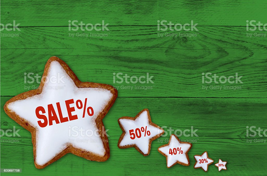 Sale cinnamon star on green wood concept stock photo