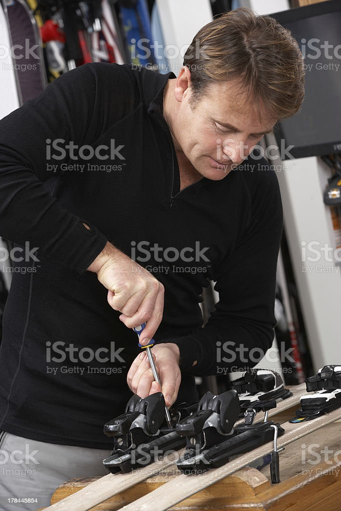 Sales Assistant Adjusting Fittings On Skis In Hire Shop stock photo