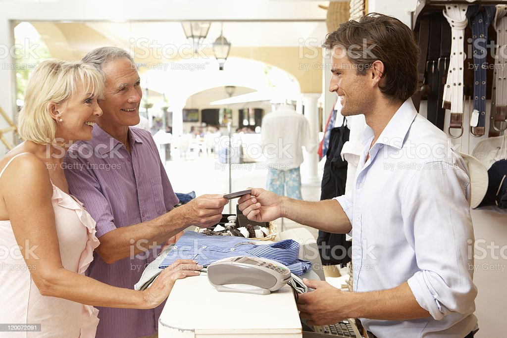 Sales Assistant At Checkout Of Clothing Store Serving Customers royalty-free stock photo