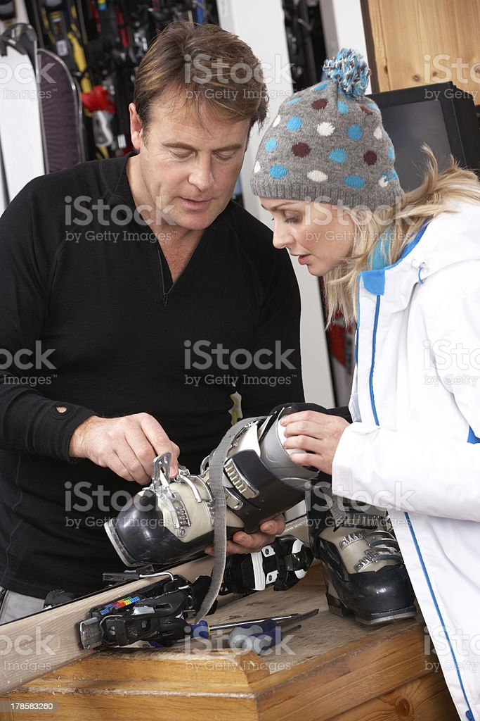 Sales Assistant Helping Advising Female Customer On Ski Boots stock photo