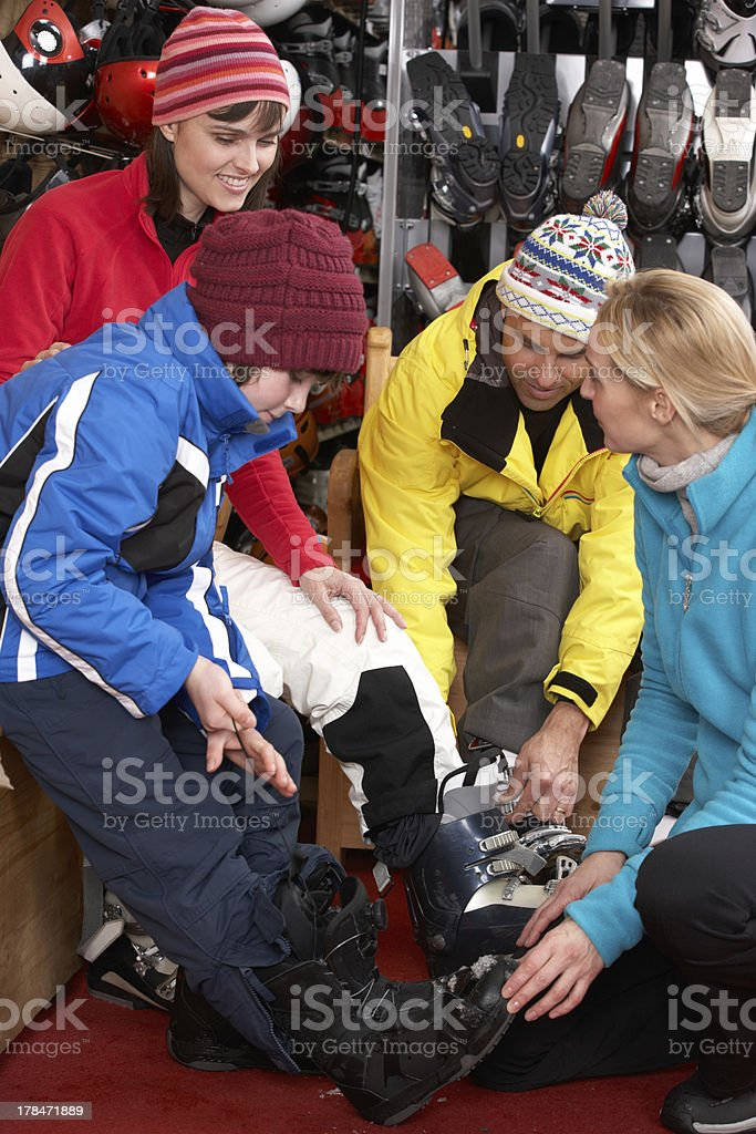 Sales Assistant Helping Family To Try On Ski Boots stock photo