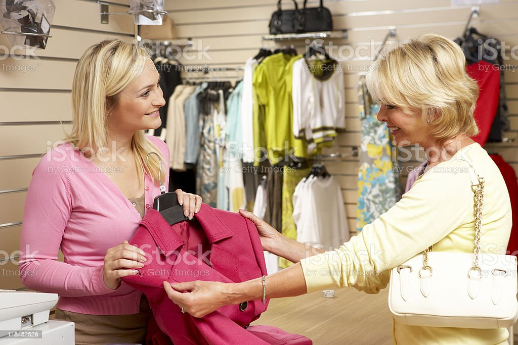 Sales assistant with customer in clothing store stock photo