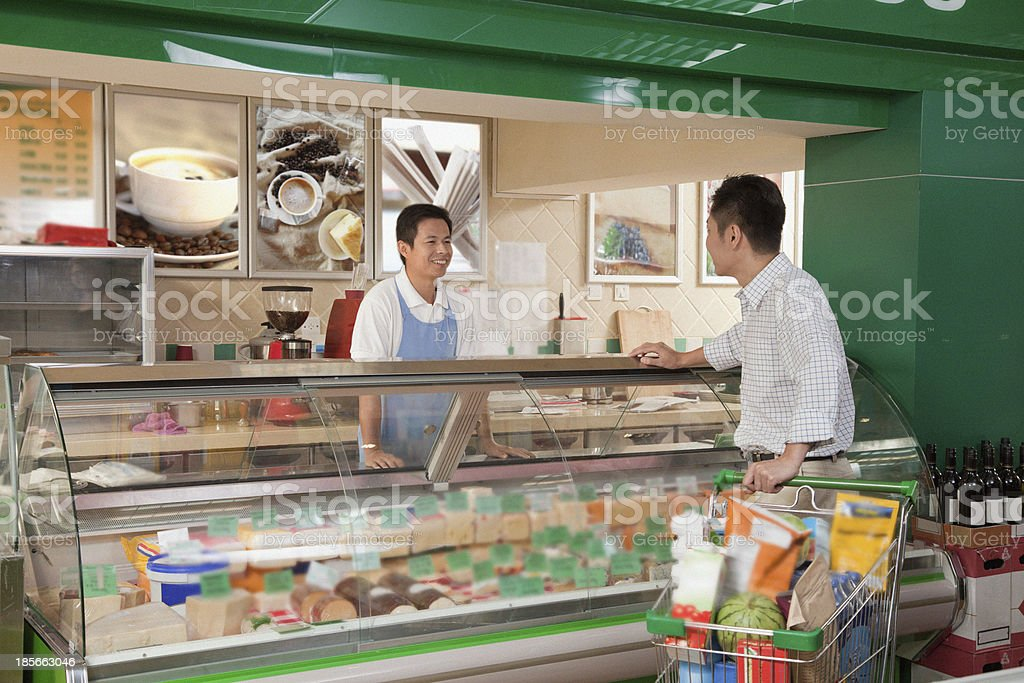 Sales Clerk assisting man at the Deli counter, Beijing royalty-free stock photo