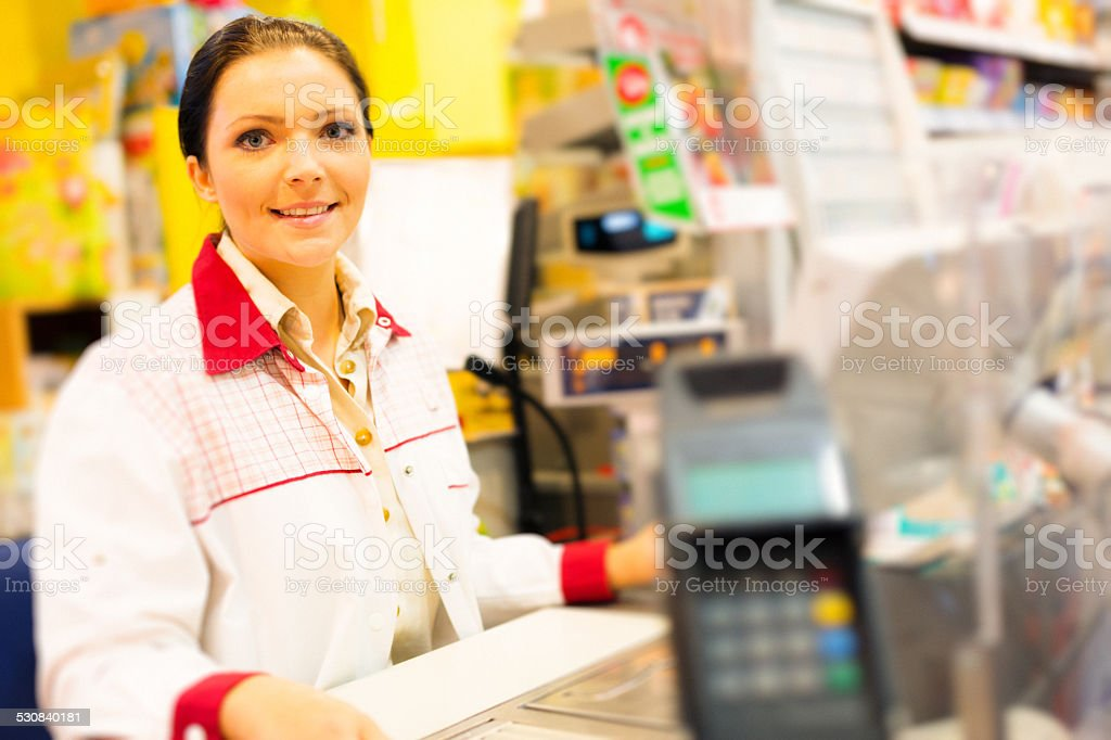 sales clerk at a cash register in the supermarket stock photo