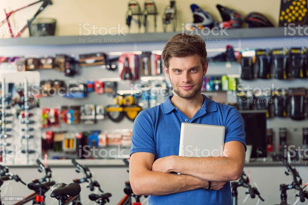 Sales clerk with digital tablet in bike shop stock photo