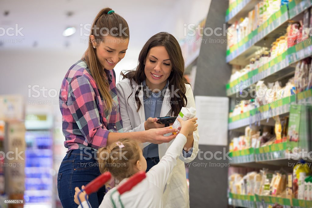 Sales clerk with mother and daughter stock photo