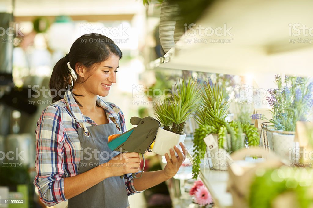 Sales clerk working with price gun in a shop stock photo