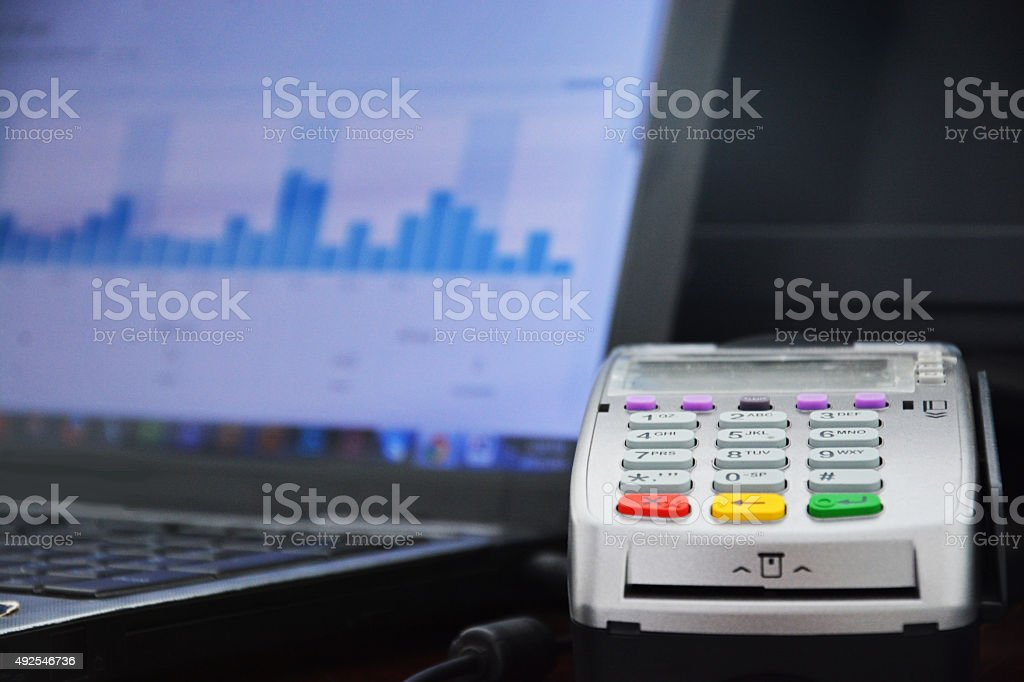 Sales - payment terminal with payment report displayd on laptop stock photo