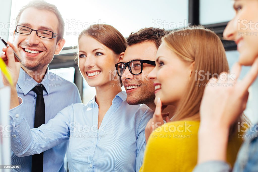 Sales reps looking at their results presented on a board stock photo